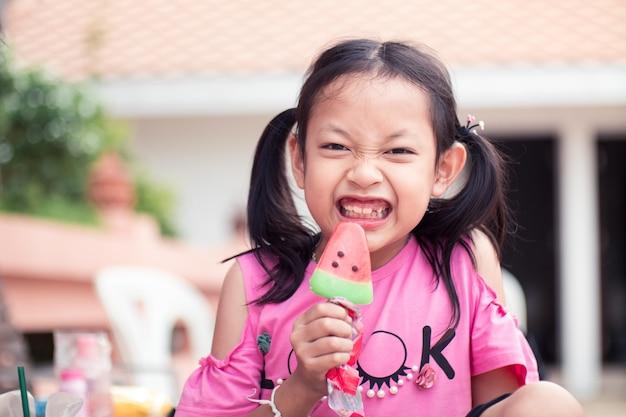 Muchacha asiática del niño que sonríe y feliz con comer el helado