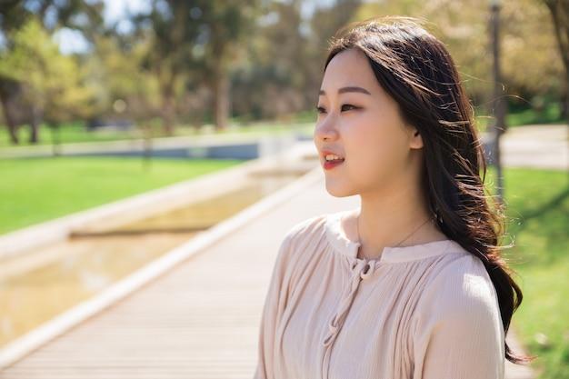 Muchacha asiática pensativa que disfruta de paisaje en parque de la ciudad