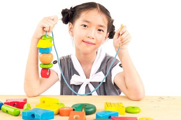La muchacha asiática preciosa es juguete colorido del bloque de madera del juego