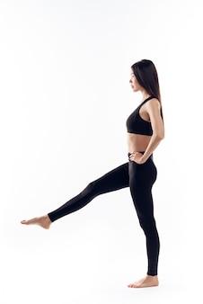 Muchacha asiática que se coloca en una pierna. concepto de aerobic.