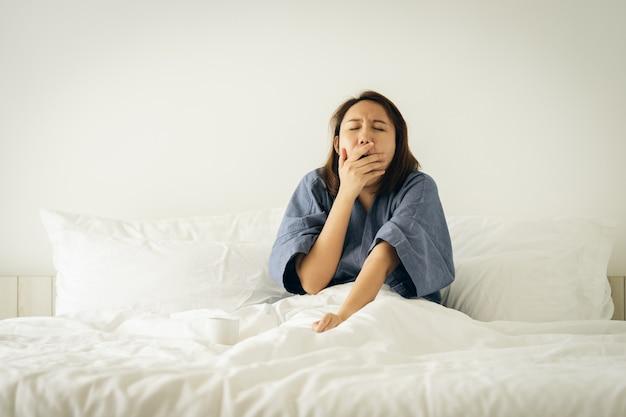 Muchacha asiática que estira el cuerpo después de despertarse por la mañana. hazlo más brillante