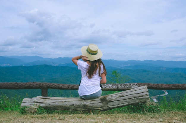 Muchacha asiática que se sienta en la madera y que mira la opinión mountian