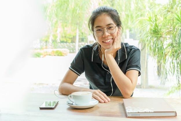 Muchacha asiática que sonríe usando el auricular con la taza de café que mira la cámara.