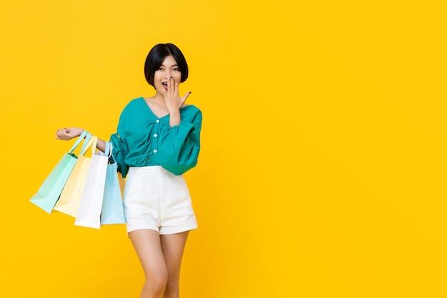 Muchacha asiática shopaholic alegre joven con bolsas de la compra