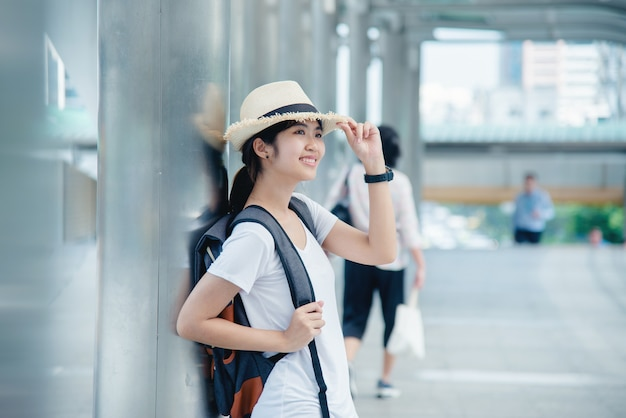 Muchacha asiática sonriente feliz del estudiante con la mochila en el fondo de la ciudad