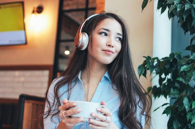 La muchacha asiática sonriente de la morenita encantadora hermosa en auriculares con la taza de café o de té adentro disfruta de música en café