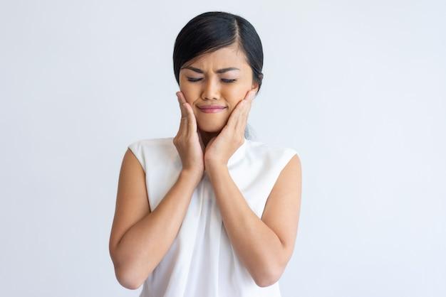 Muchacha asiática sonriente que disfruta del efecto de la crema facial