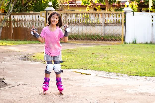 Muchacha asiática sonriente que juega a patinar en casa. fondo de ocio deportivo.