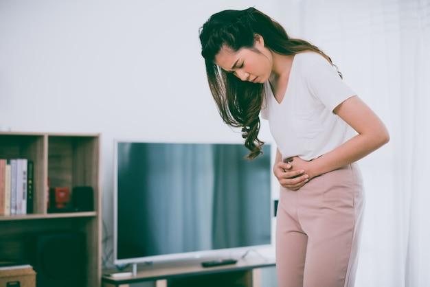 La muchacha asiática está teniendo dolor de estómago en su hogar.