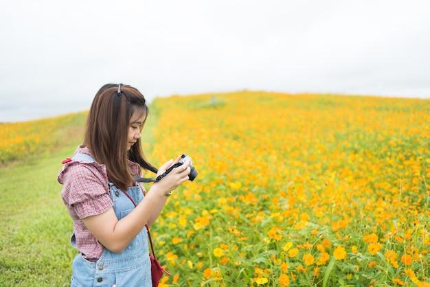 La muchacha asiática toma la foto que florece las flores amarillas, concepto del recorrido