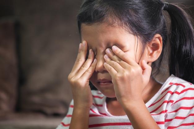 La muchacha asiática triste del niño está llorando y se está frotando los ojos con sus manos
