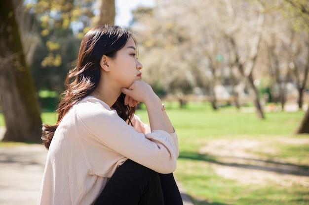 Muchacha asiática triste pensativa que consigue azules en parque de la primavera