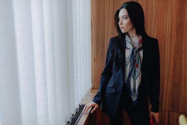 La muchacha atractiva emocional joven en businessstyle viste en una ventana con un teléfono en una oficina o un auditorio moderna