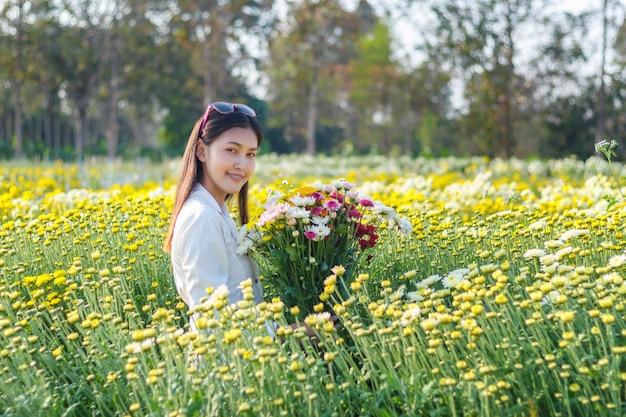 Muchacha atractiva hermosa con la flor colorida en parque
