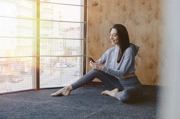 Muchacha atractiva joven de la aptitud que se sienta en el piso cerca de la ventana en el fondo de una pared de madera