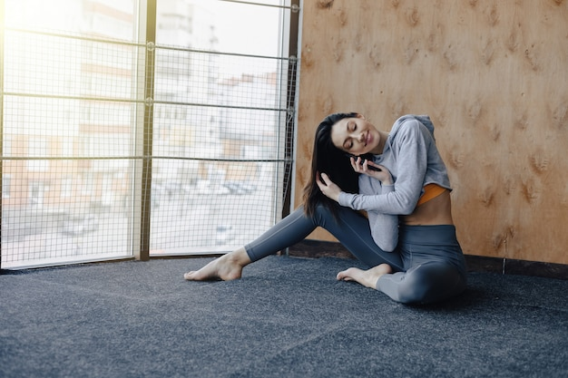 Muchacha atractiva joven de la aptitud que se sienta en el piso cerca de la ventana en el fondo de una pared de madera.