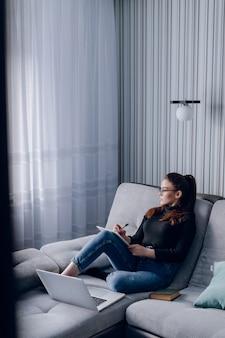 Muchacha atractiva joven en casa que trabaja con la computadora portátil en el sofá. comodidad y comodidad en casa. oficina en casa y trabajo desde casa. empleo remoto en línea.