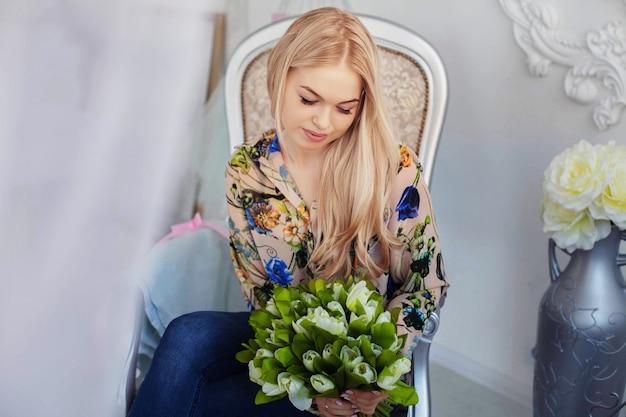 Muchacha atractiva joven con las flores.