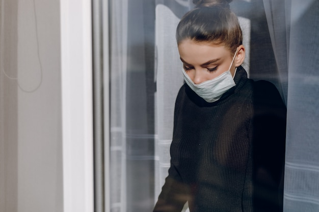 La muchacha atractiva joven en una máscara médica protectora mira por la ventana. aislamiento durante la epidemia. aislamiento en casa.