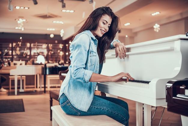 La muchacha atractiva joven está tocando el piano en tienda de la música.