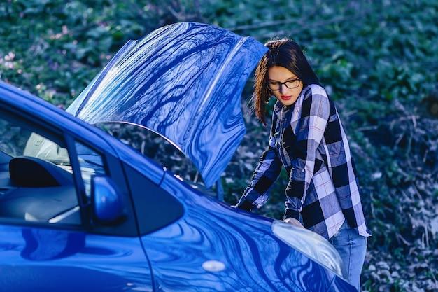 La muchacha atractiva repara el coche en el camino