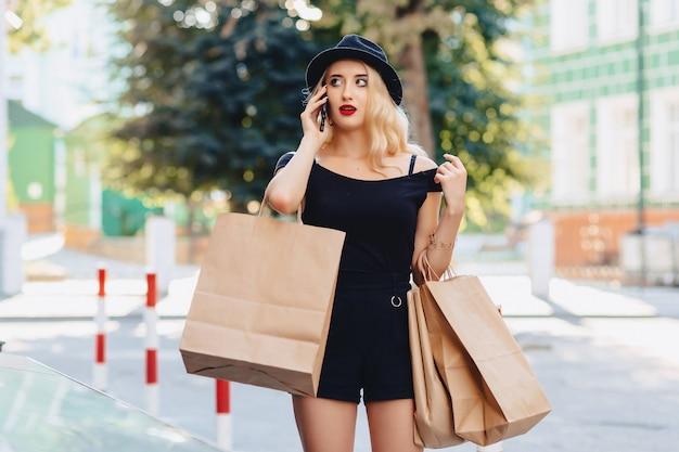 Muchacha atractiva rubia en un sombrero después de hacer compras en los rayos del sol del verano con el teléfono