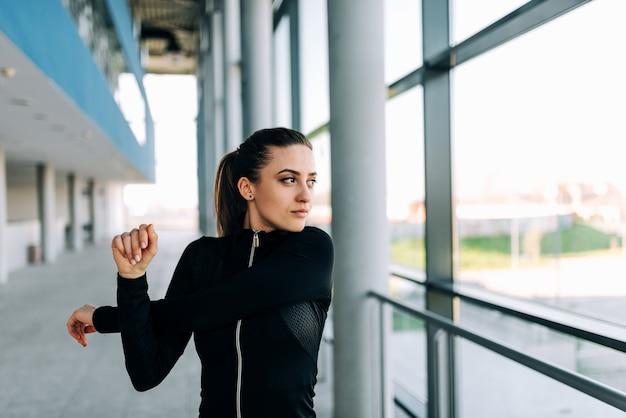 Muchacha atractiva en sportwear negro que estira los brazos. de cerca.