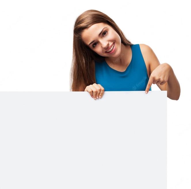 Muchacha atractiva sujetando un cartel en blanco