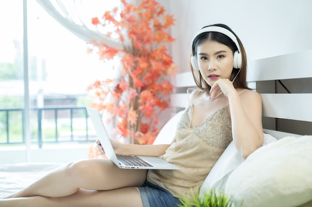 Muchacha con los auriculares que escuchan la música en una computadora portátil en la cama en casa