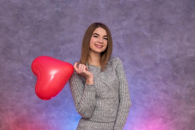 Muchacha de la belleza con tiro del estudio del globo de aire en forma de corazón rojo