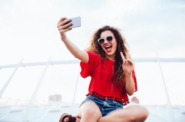 La muchacha bonita alegre con el pelo rizado toma un selfie en el teléfono móvil