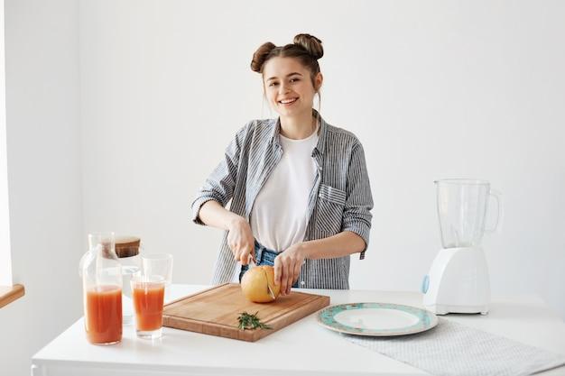 Muchacha bonita alegre que sonríe cortando el pomelo para el desayuno sobre la pared blanca. batido de desintoxicación saludable. comida de fitness.