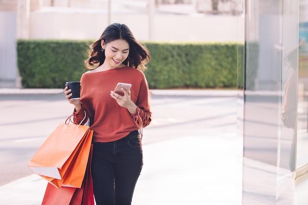 Muchacha bonita asiática feliz que sostiene los panieres en concepto de la alameda de compras.