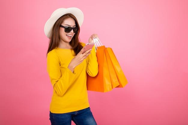 Muchacha bonita asiática feliz que sostiene los panieres y el teléfono elegante que miran lejos en el fondo rosado, concepto colorido de las compras.