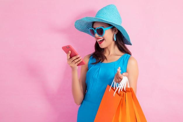 Muchacha bonita asiática feliz que sostiene los panieres y el teléfono elegante que miran lejos en fondo rosado