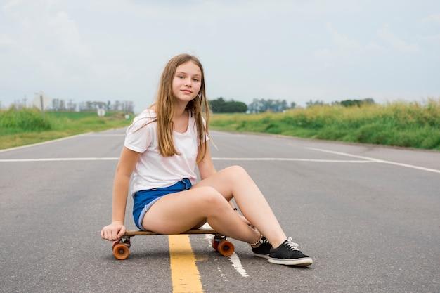Muchacha bonita atractiva moderna que se sienta en el monopatín en el camino vacío