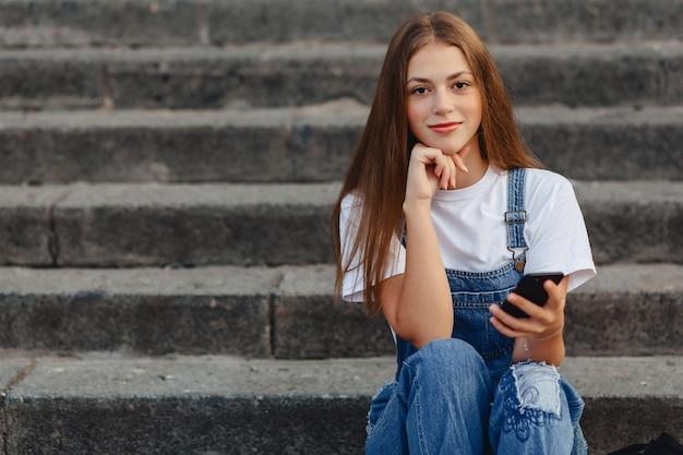 Muchacha bonita joven con la cartera que se sienta en las escaleras y que escribe sms en el teléfono