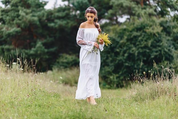Muchacha bonita joven con la flor en paseo ligero del vestuario en el césped cerca del bosque del verano