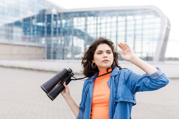 La muchacha bonita joven mira lejos con un binocular en sus manos.