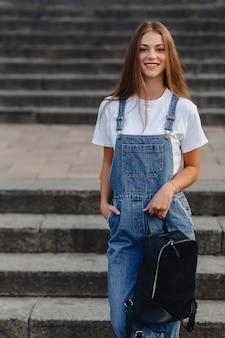 Muchacha bonita joven con el paseo de la cartera en la calle cerca del edificio
