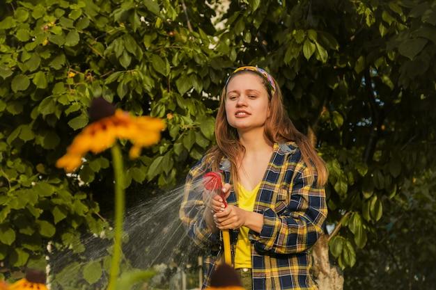 Muchacha bonita joven que se divierte en las plantas de riego del jardín con una manguera. sonriendo mientras toma un pasatiempo favorito.