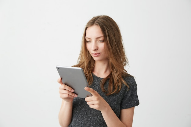 Muchacha bonita joven que sonríe mirando la tableta que navega el web de la navegación por internet.