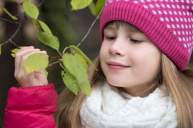 Muchacha bonita del niño que lleva la ropa caliente del invierno que sostiene la rama de árbol con las hojas verdes en tiempo frío al aire libre.