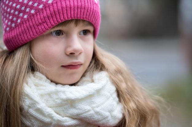 Muchacha bonita del niño en ropa de invierno hecha punto caliente al aire libre