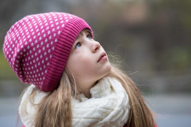 Muchacha bonita del niño en ropa de invierno de punto caliente al aire libre.