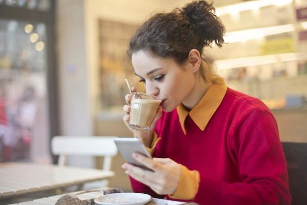 Muchacha bonita que bebe el café y que comprueba su smartphone