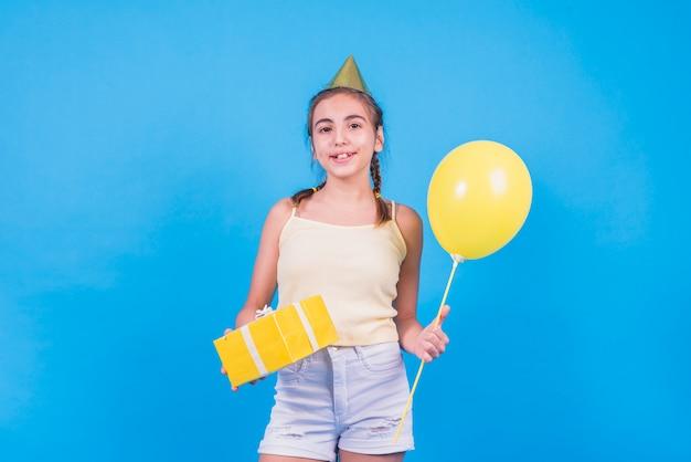 Muchacha bonita que se coloca con la caja y los globos de regalo en el papel pintado azul