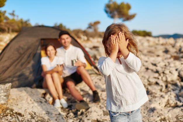 Muchacha bonita que se coloca en la playa rocosa y los ojos cerrados que cubren la cara con la mano.