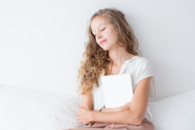 Muchacha bonita que dormita y que se sienta en cama con el libro