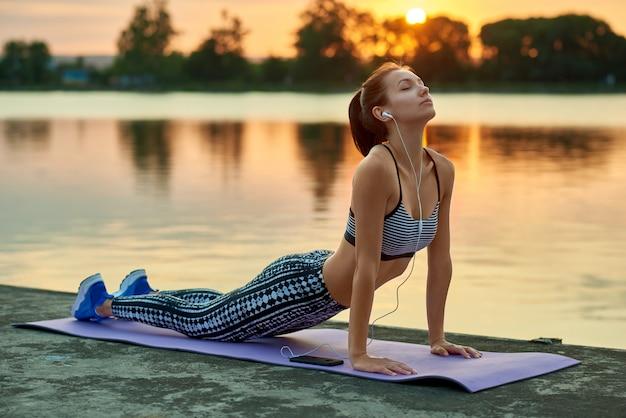 La muchacha bonita que hace yoga ejercita puesta del sol blanca del verano cerca del lago de la ciudad
